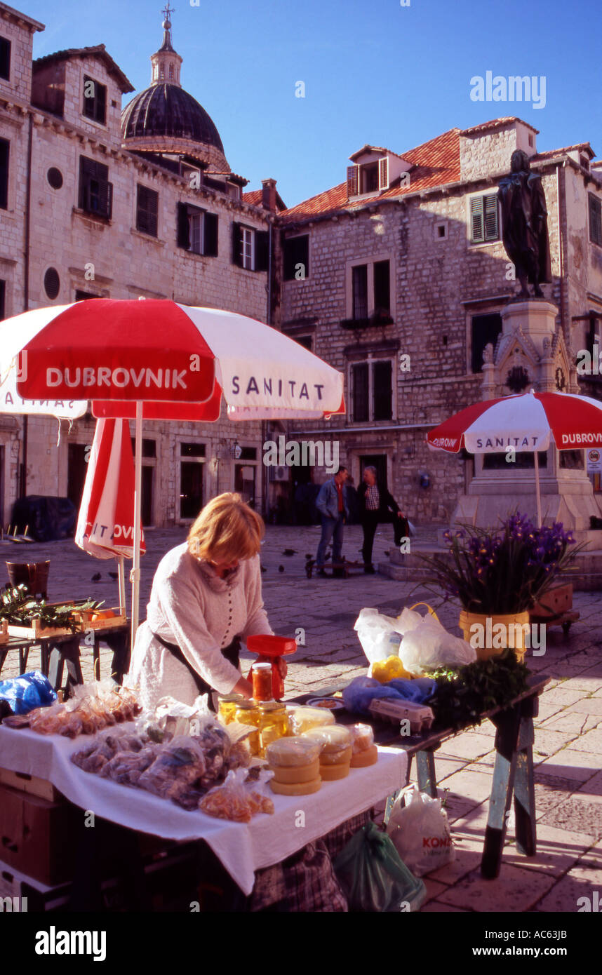 A Croatian woman arranging her stall at the open air market in Gundulic Square Dubrovnik Old Town Croatia - Stock Image