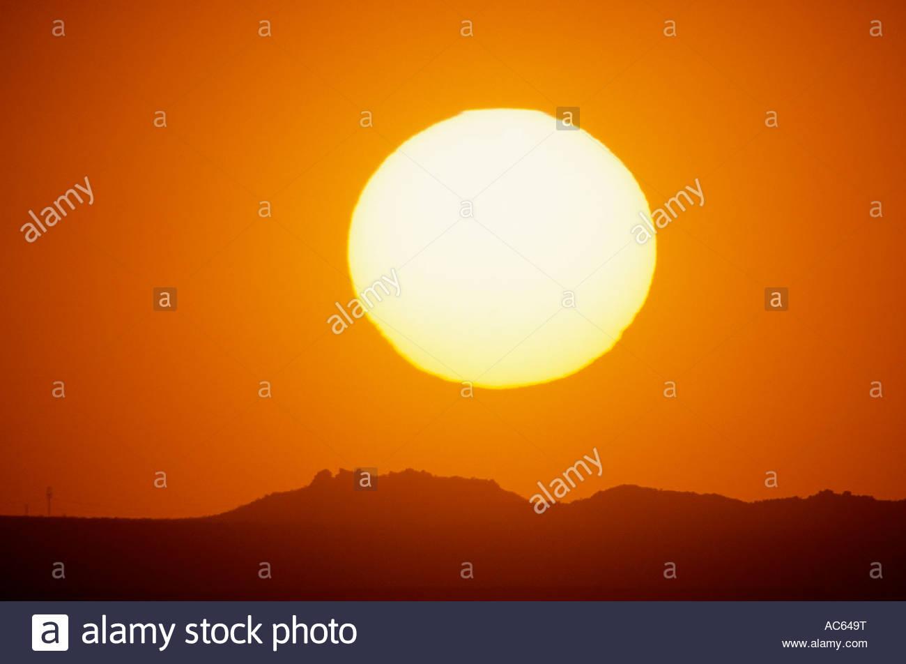 The glowing hot desert sun setting on mountains south of Tucson Arizona sunset orange - Stock Image