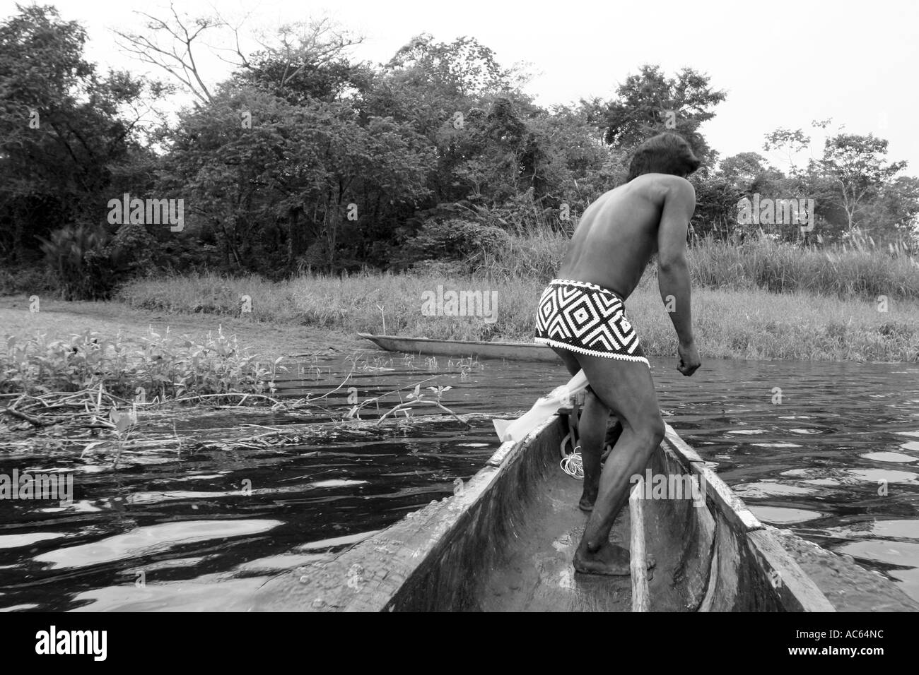 An Embera indian sailing through the Chagres river in the Panamenian jungle Chagres National Park in his canoe - Stock Image