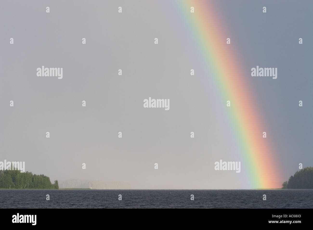 The end of the rainbow hitting spit of land in a lake , Finland Stock Photo