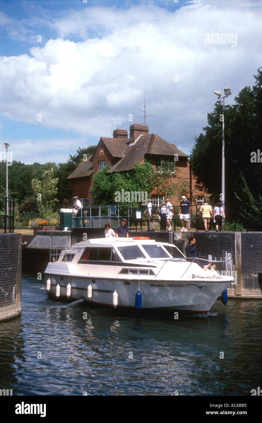 A motor cruiser leaves Hambleden Lock on the River Thames in Oxfordshire England UK Stock Photo