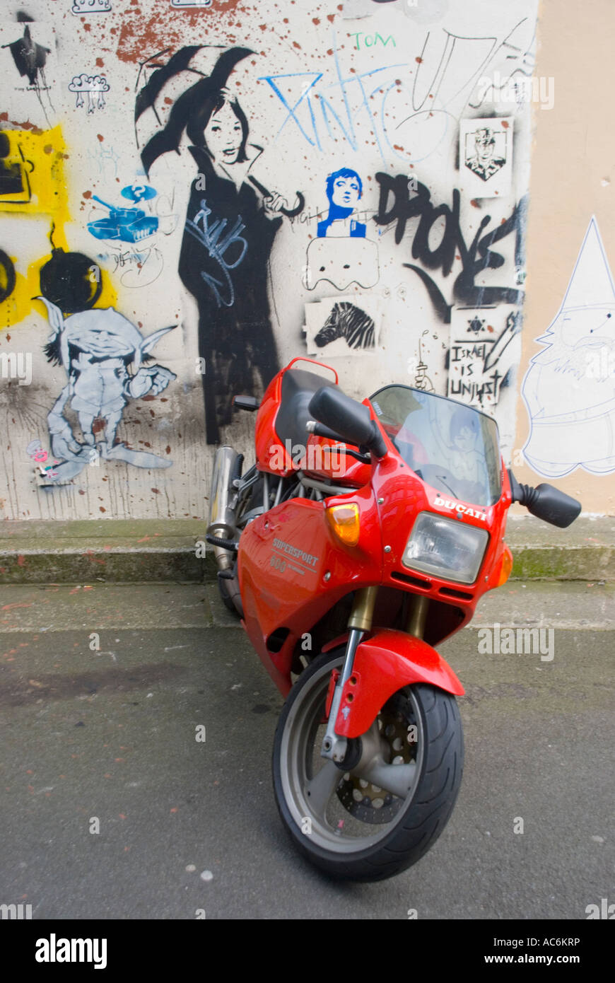 Red Ducati Supersport 600 and wall art graffiti - Stock Image