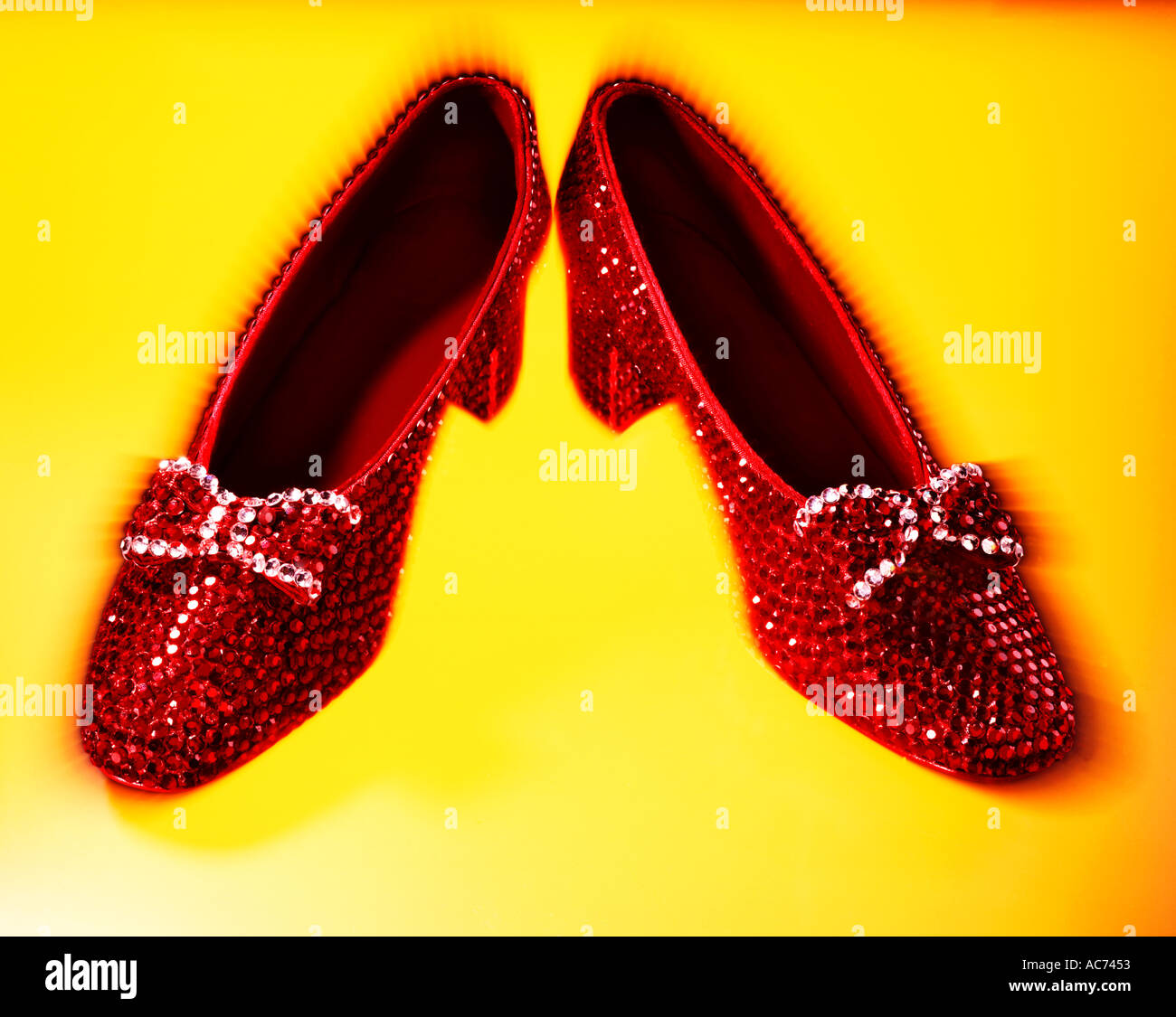 08baaecc427 red ruby slippers with bows on yellow background - Stock Image