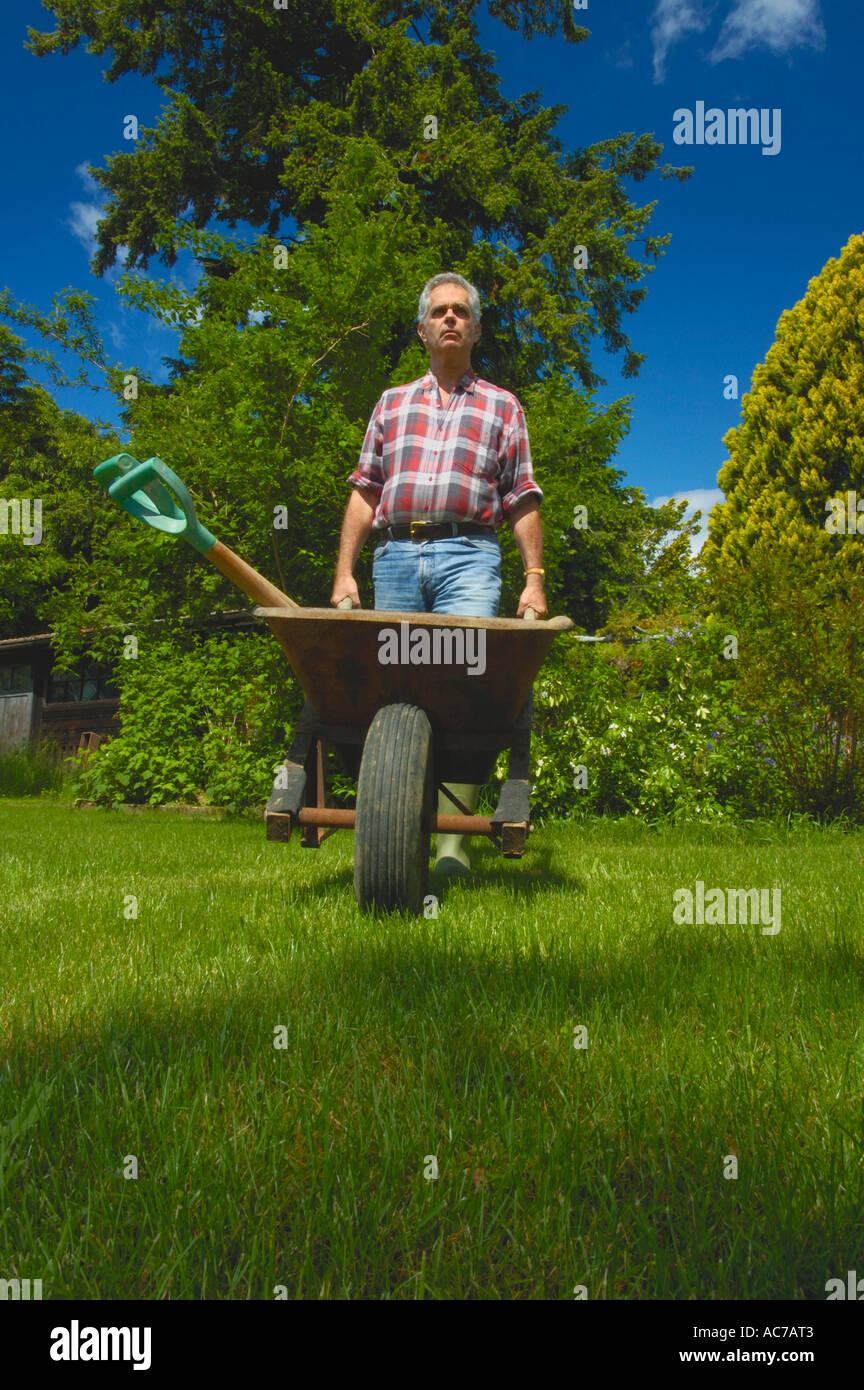 Gardener with wheelbarrow. - Stock Image