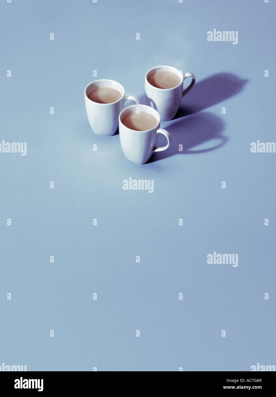 Three white mugs on a pale blue background - Stock Image