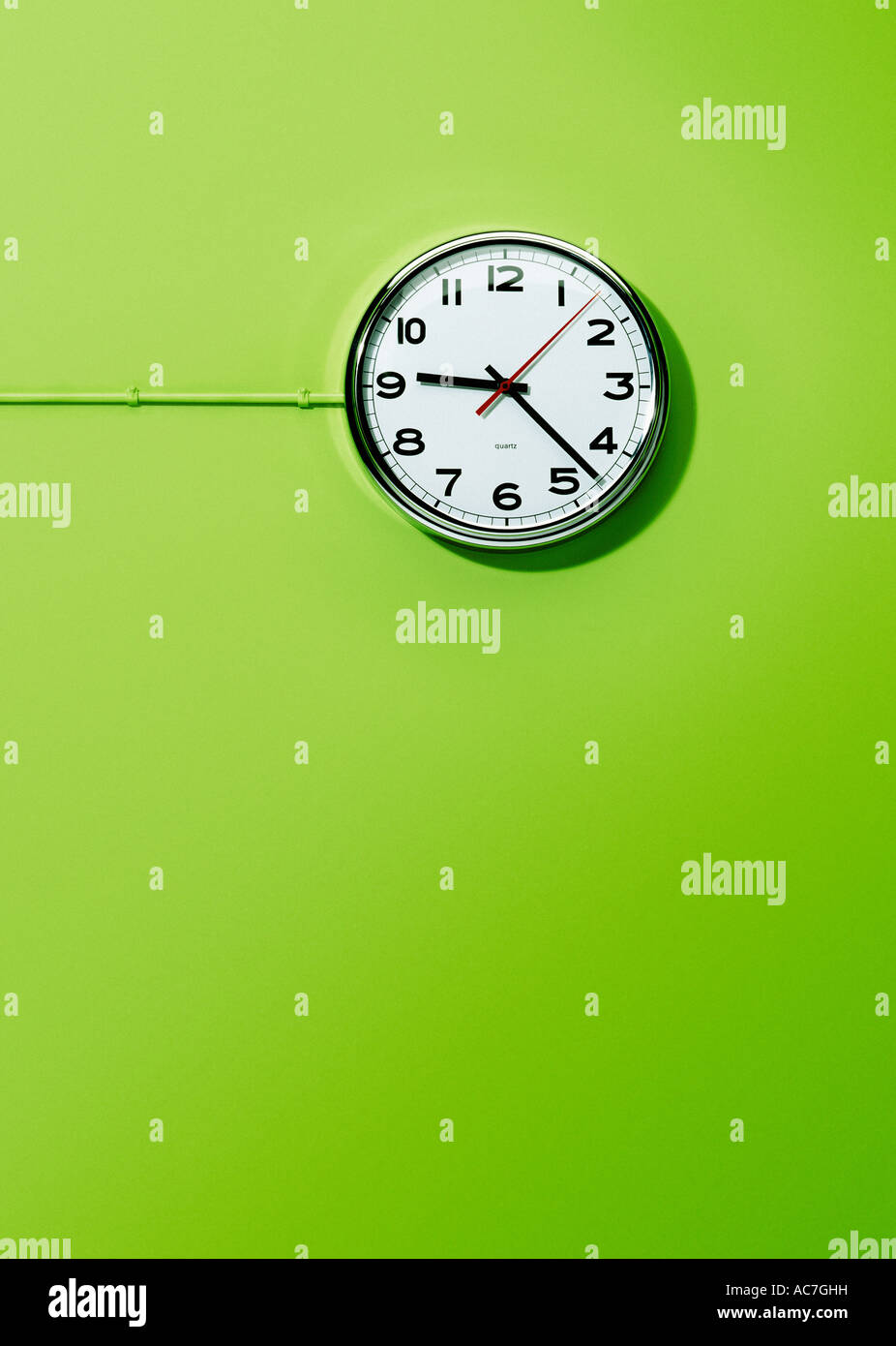 Wall mounted electric office clock against a lime green background - Stock Image