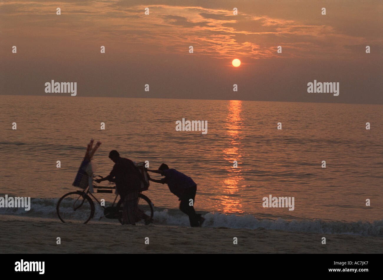 Silhouette of vendors on Alappuzha beach at sunset in  Kerala - Stock Image