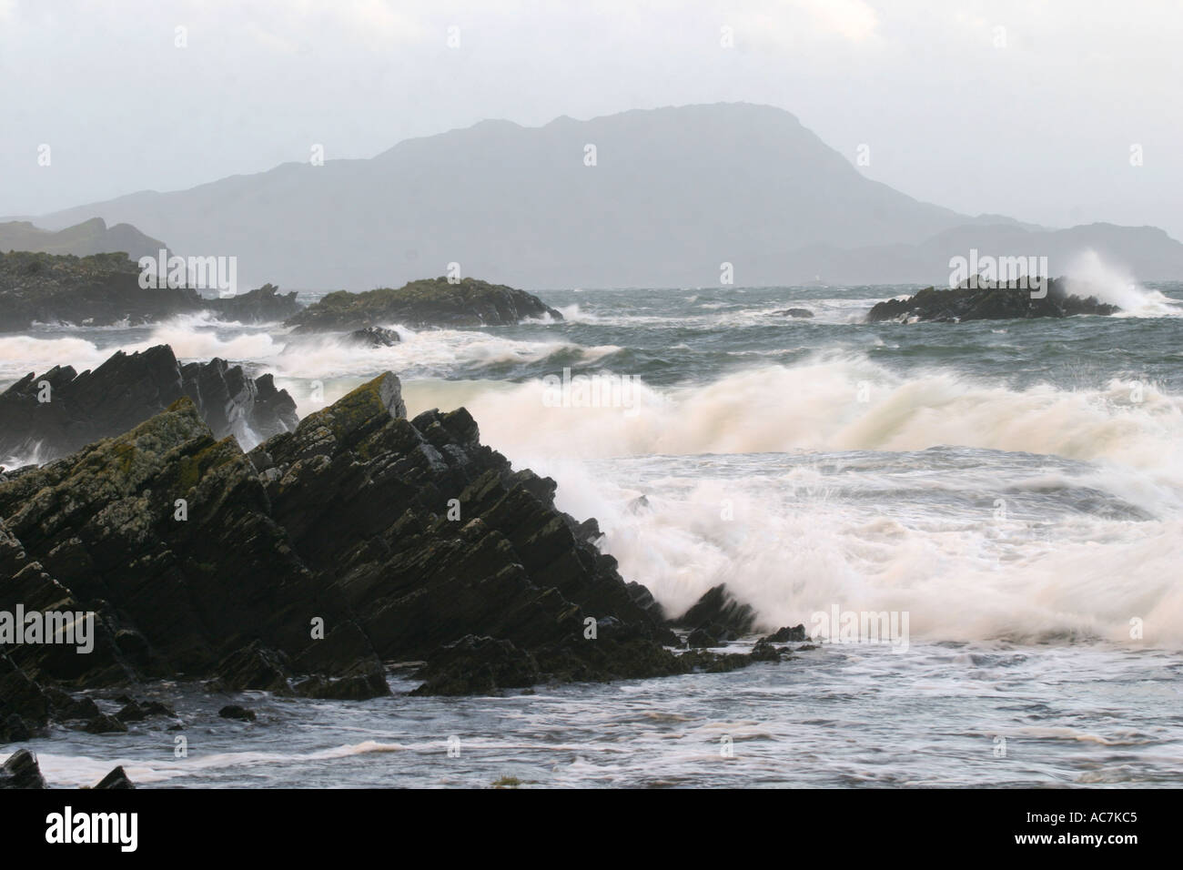 Hurricane waves crash into the rocky shore near Easdale,  Oban in January 2005 - Stock Image