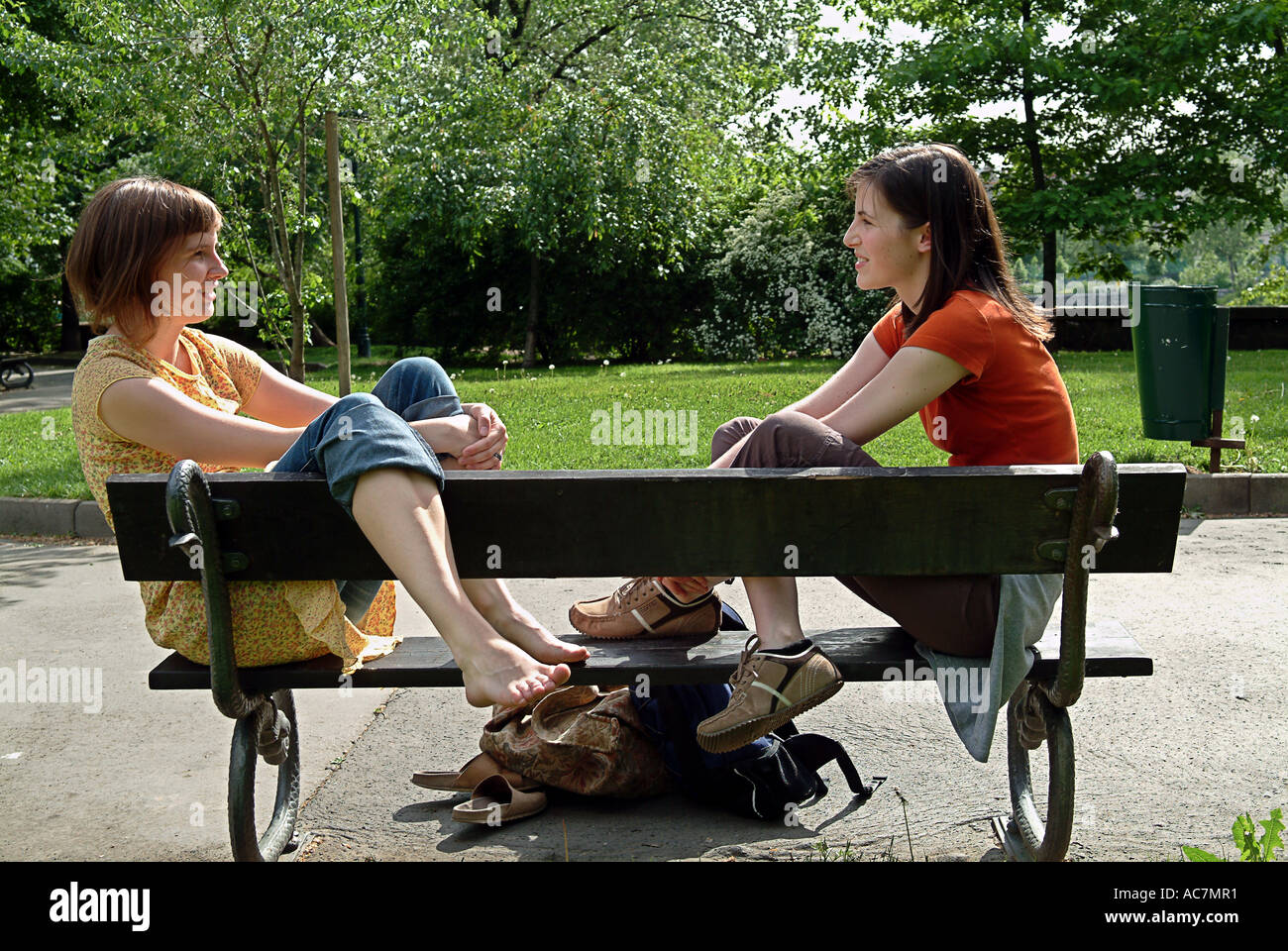 Two girls talking to each other on a bench - Stock Image