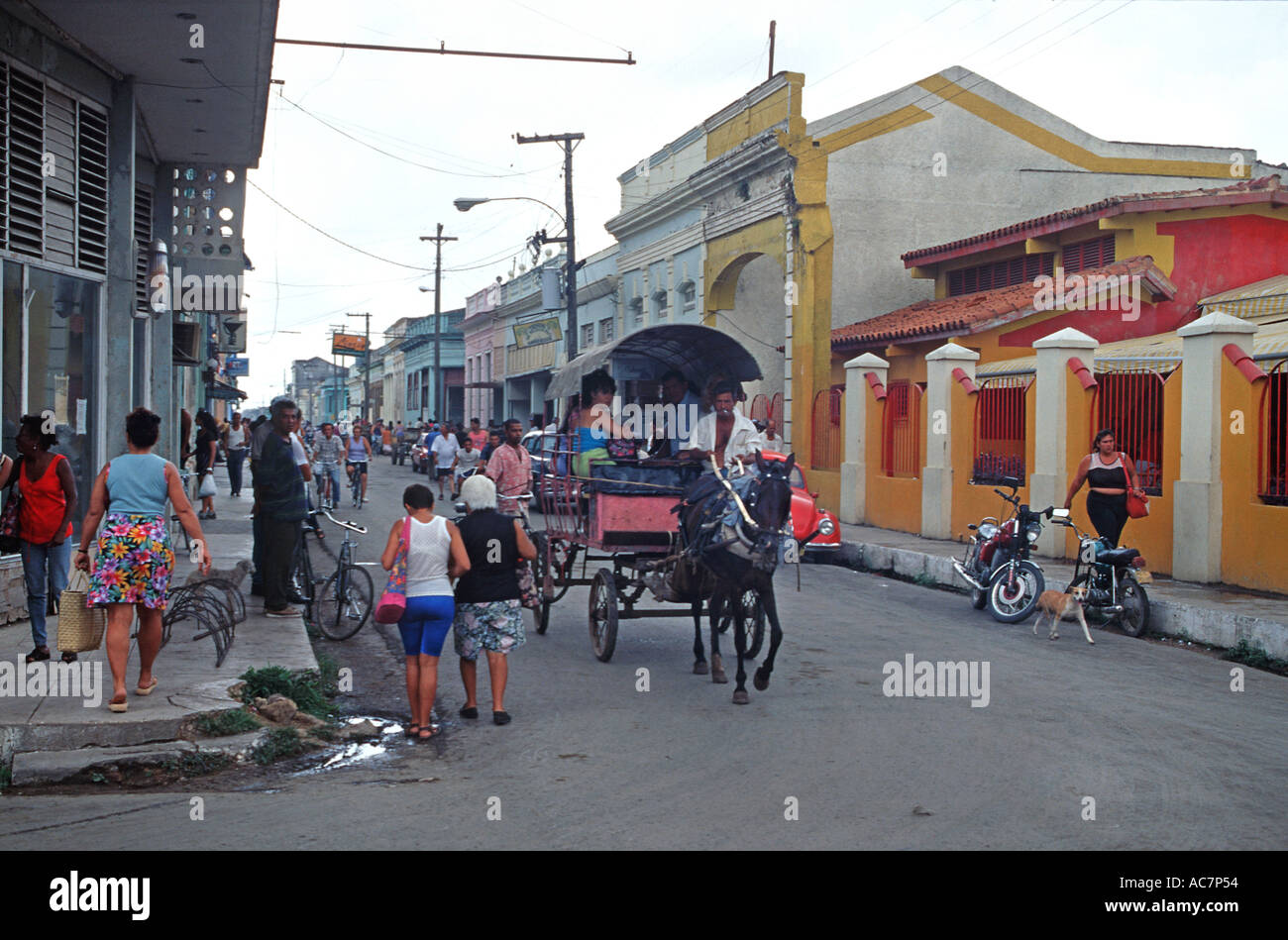 Street scene in Cardenas Cuba Horse drawn carriage in the street Brightly painted colonial buildings Cuba - Stock Image