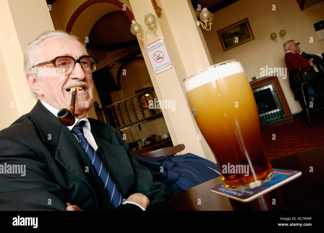 Elderly man sucking on his unlit pipe as the No Smoking Ban comes into force with pint of beer in pub Crumlin South - Stock Image