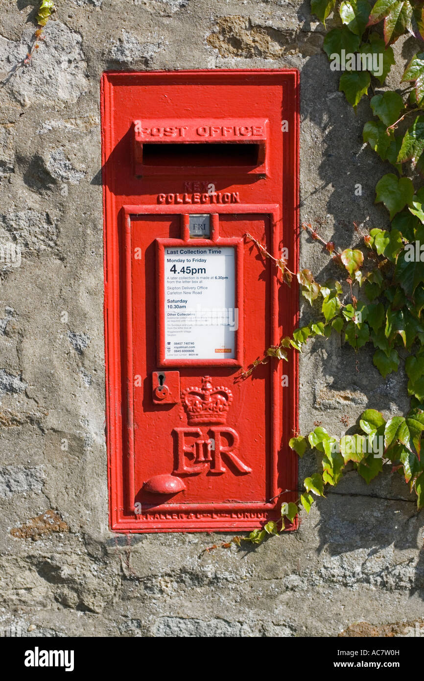 Red rectangular Post Office box set in stone wall Rathmell Yorkshire UK - Stock Image