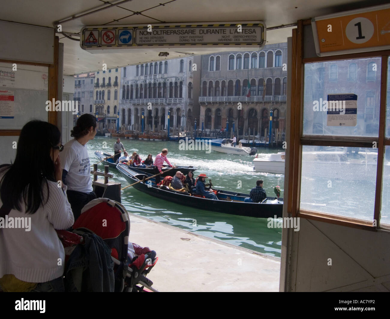 Gondolas pass a Vaporetto Stop on the Grand Canal Venice Italy - Stock Image