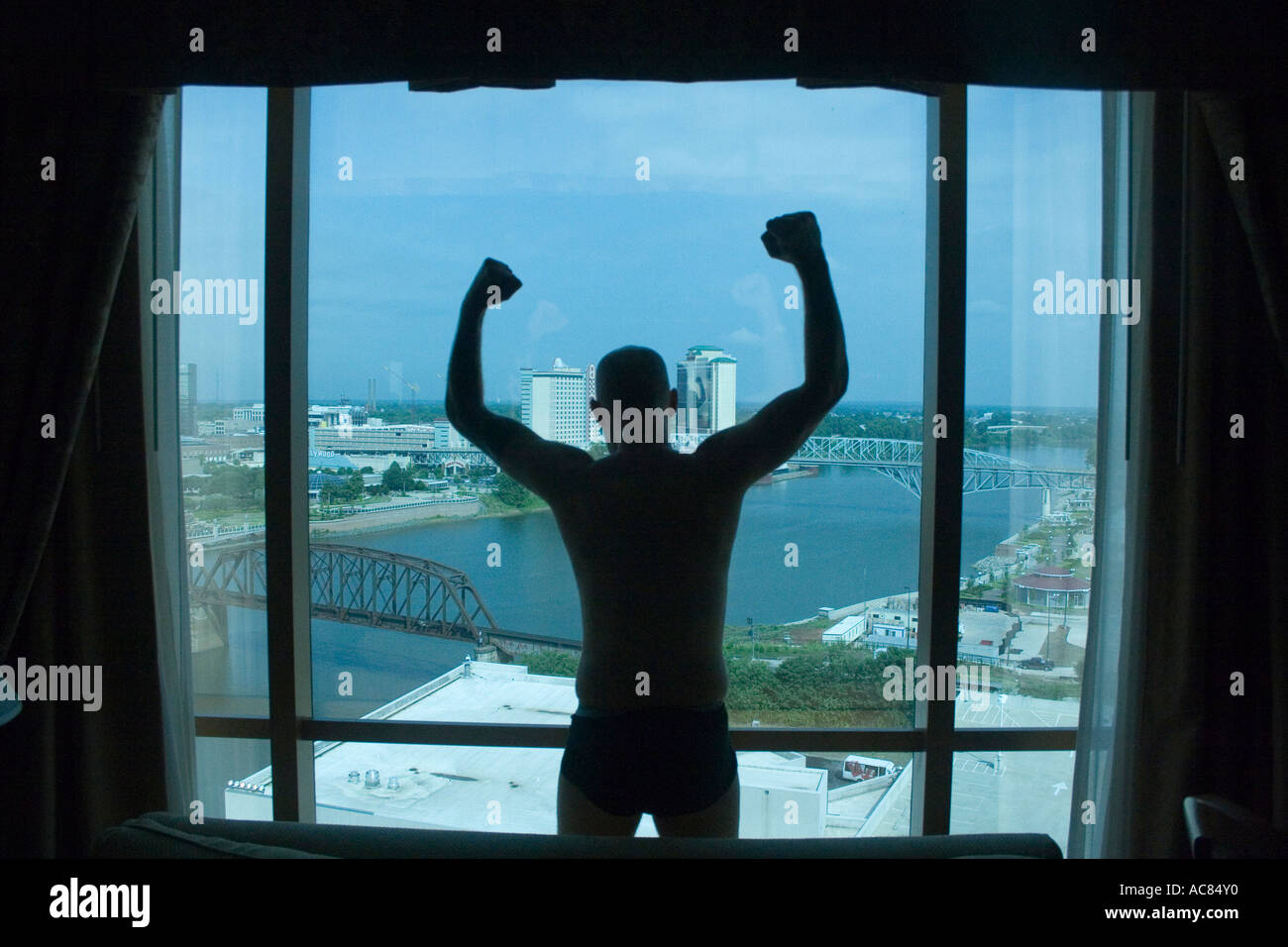 Silhouette of man raised arms looking out of hotel room. - Stock Image