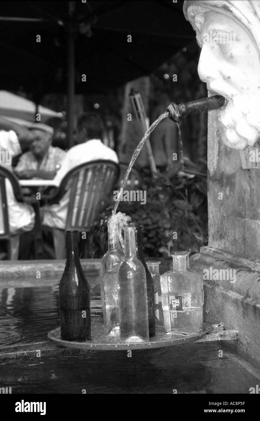 Cotignac A waiter leaves the bottles to clean themselves whilst some locals play cards in the shade Provence France - Stock Image