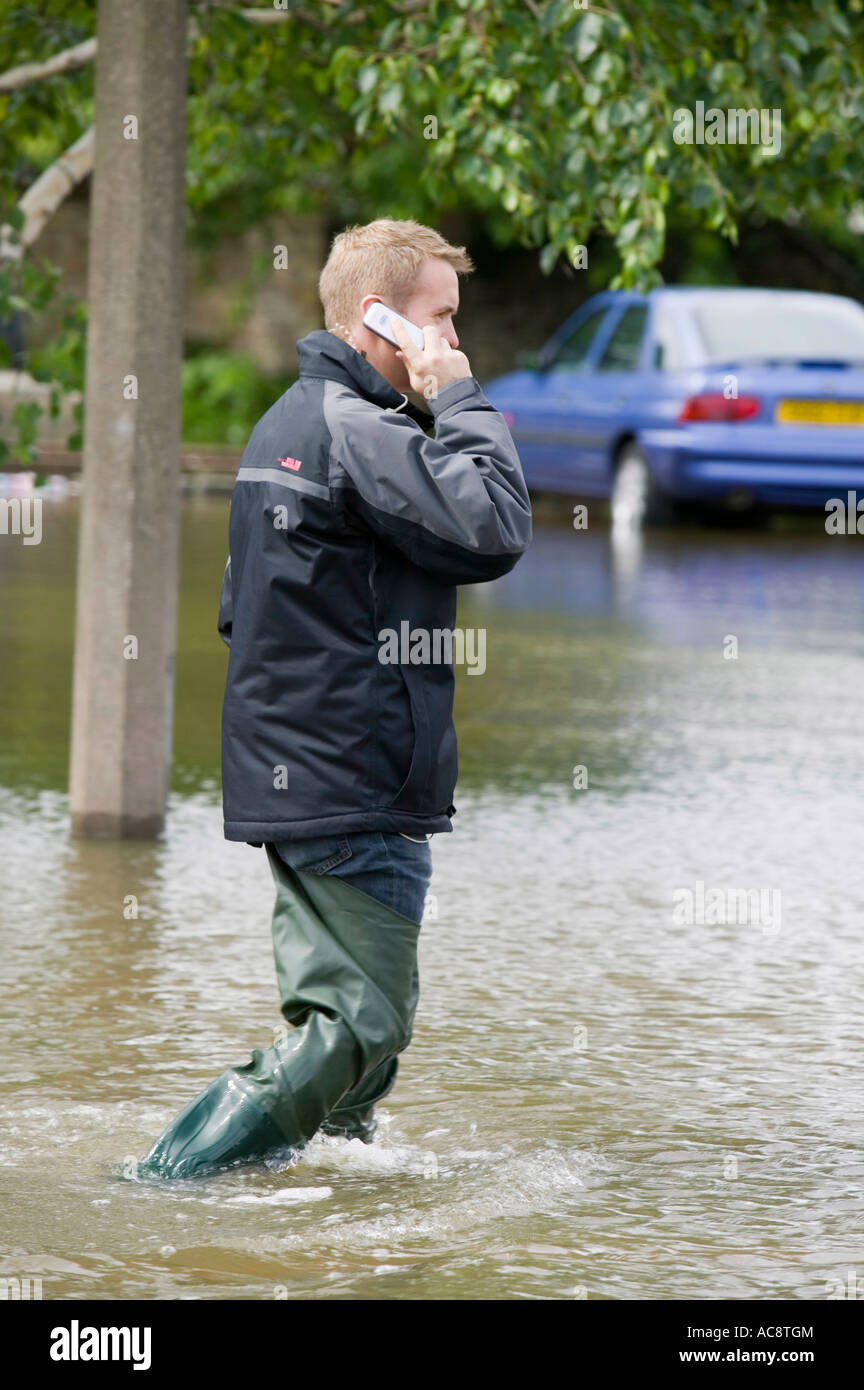 A man on a mobile phone in the unprecedented June 2007 floods in Bentley, Doncaster, UK - Stock Image