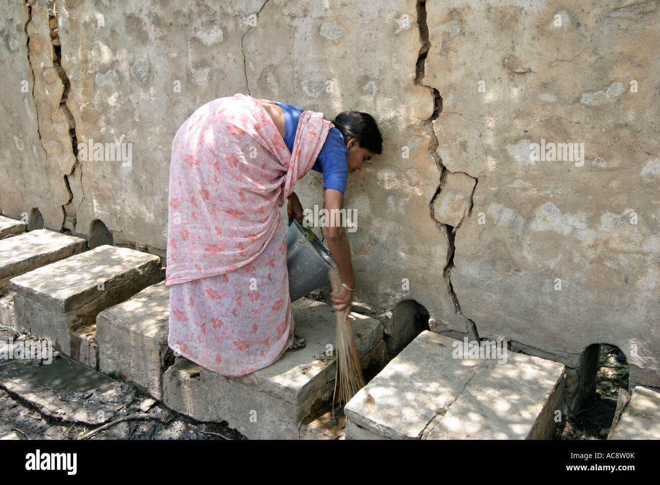 A dalit, or 'untouchable' woman, cleaning public lavatories in her town in Andhra Pradesh, India. Stock Photo