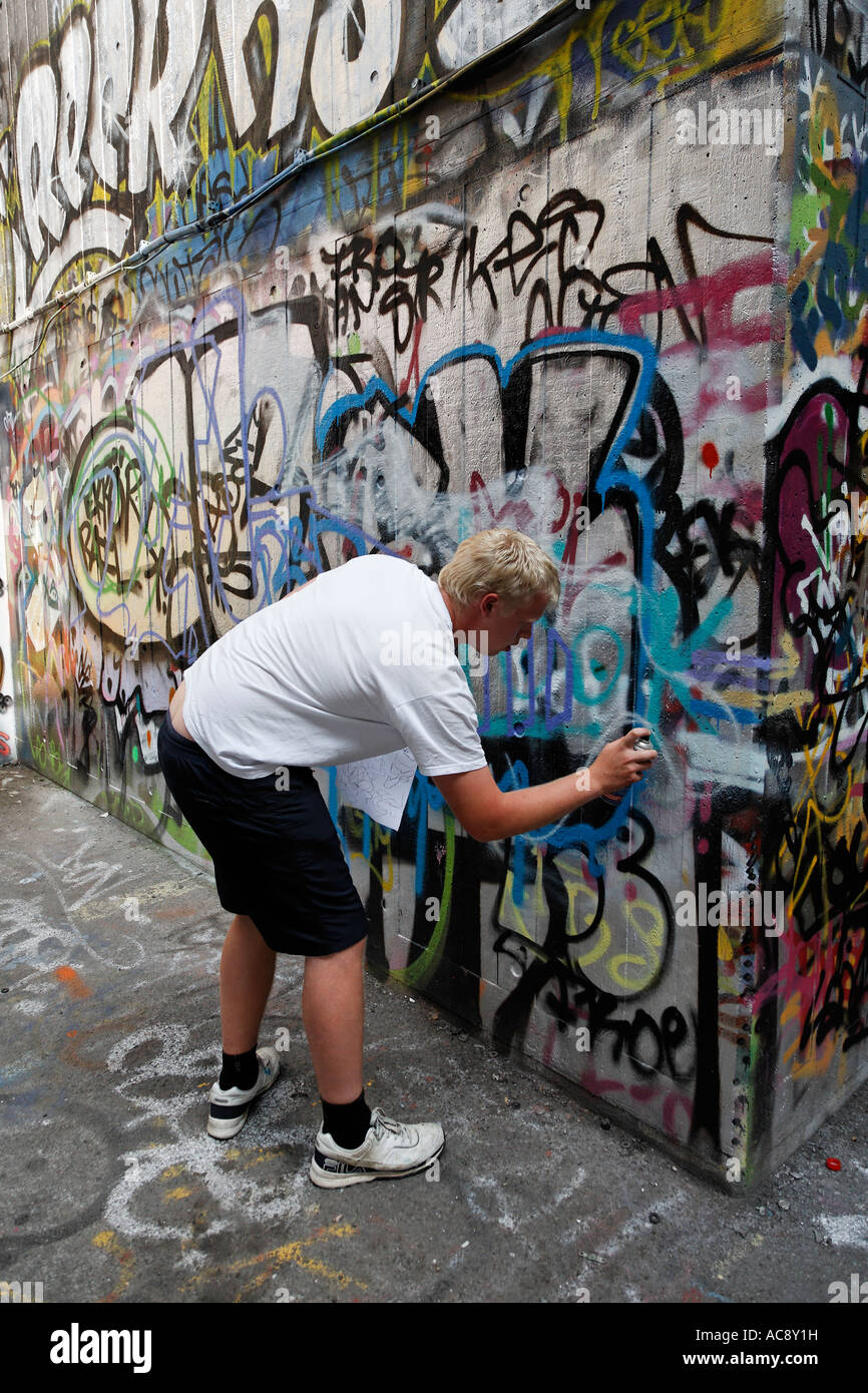 Man Painting Graffiti At The South Bank Skateboarding Center London UK  Europe   Stock Image