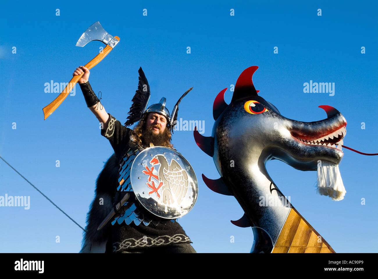 dh Up Helly Aa procession LERWICK SHETLAND Guizer Jarl Einar of Gullberuvik Viking longship galley Moogi prow man bear - Stock Image