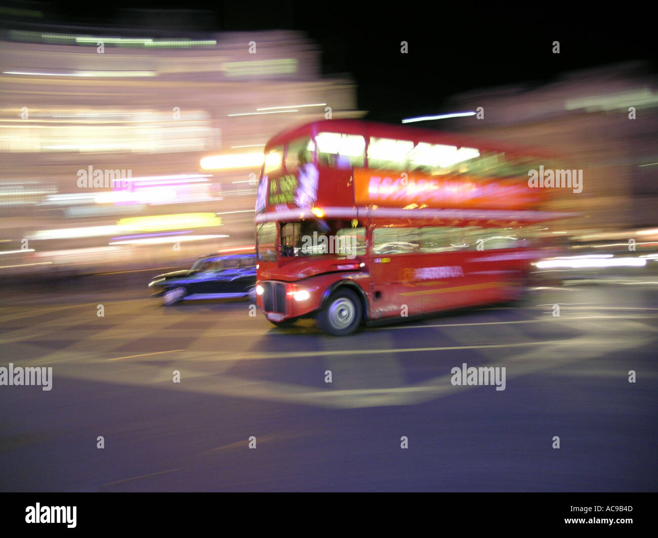 Blur of a red double decker bus at night in London England UK Britain routemaster route master - Stock Image