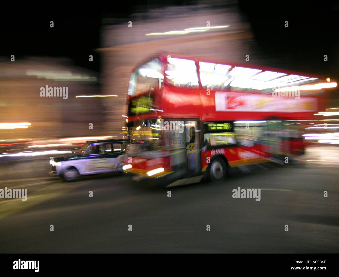 Blur of a red double decker bus at night in London England UK Britain - Stock Image