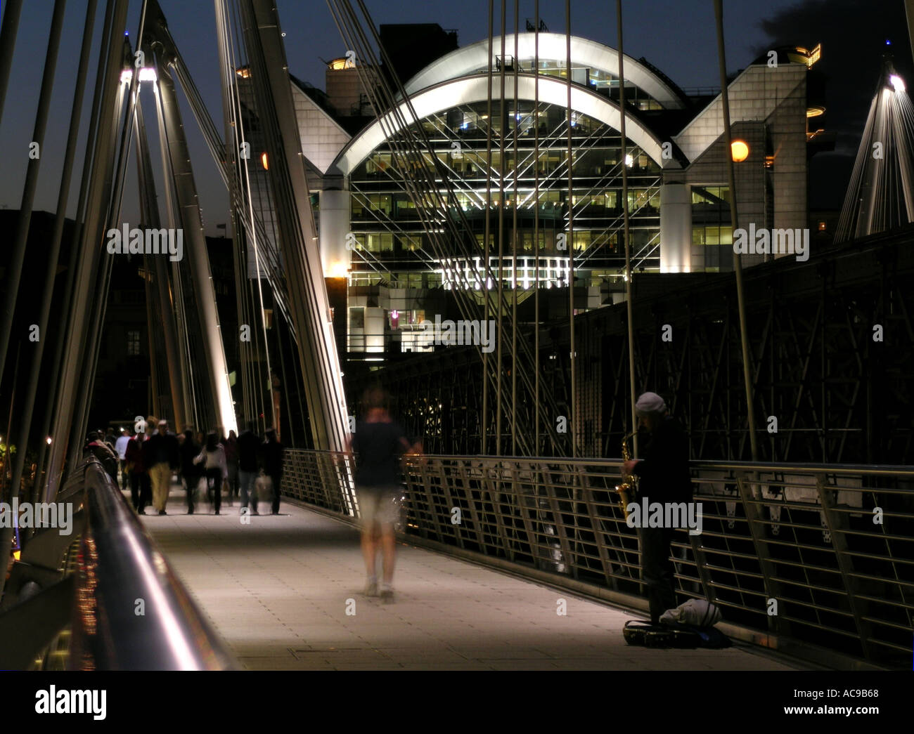 Musician on the new Hungerford Bridge also known as Jubilee Bridge in London England UK - Stock Image