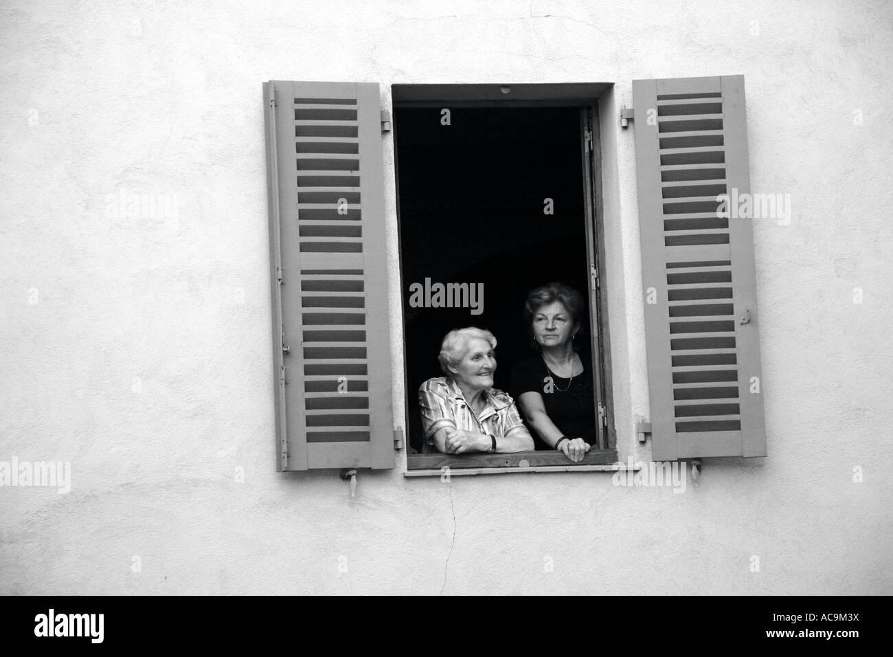 Women in a Window, Villeneuve-Loubet, France - Stock Image