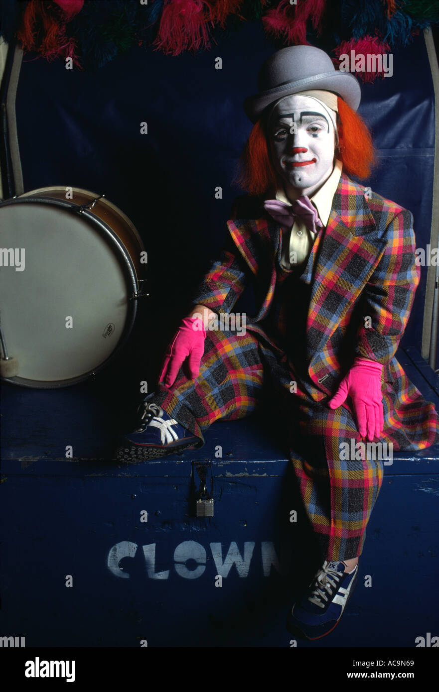 A circus clown resting between performances poses for the camera - Stock Image