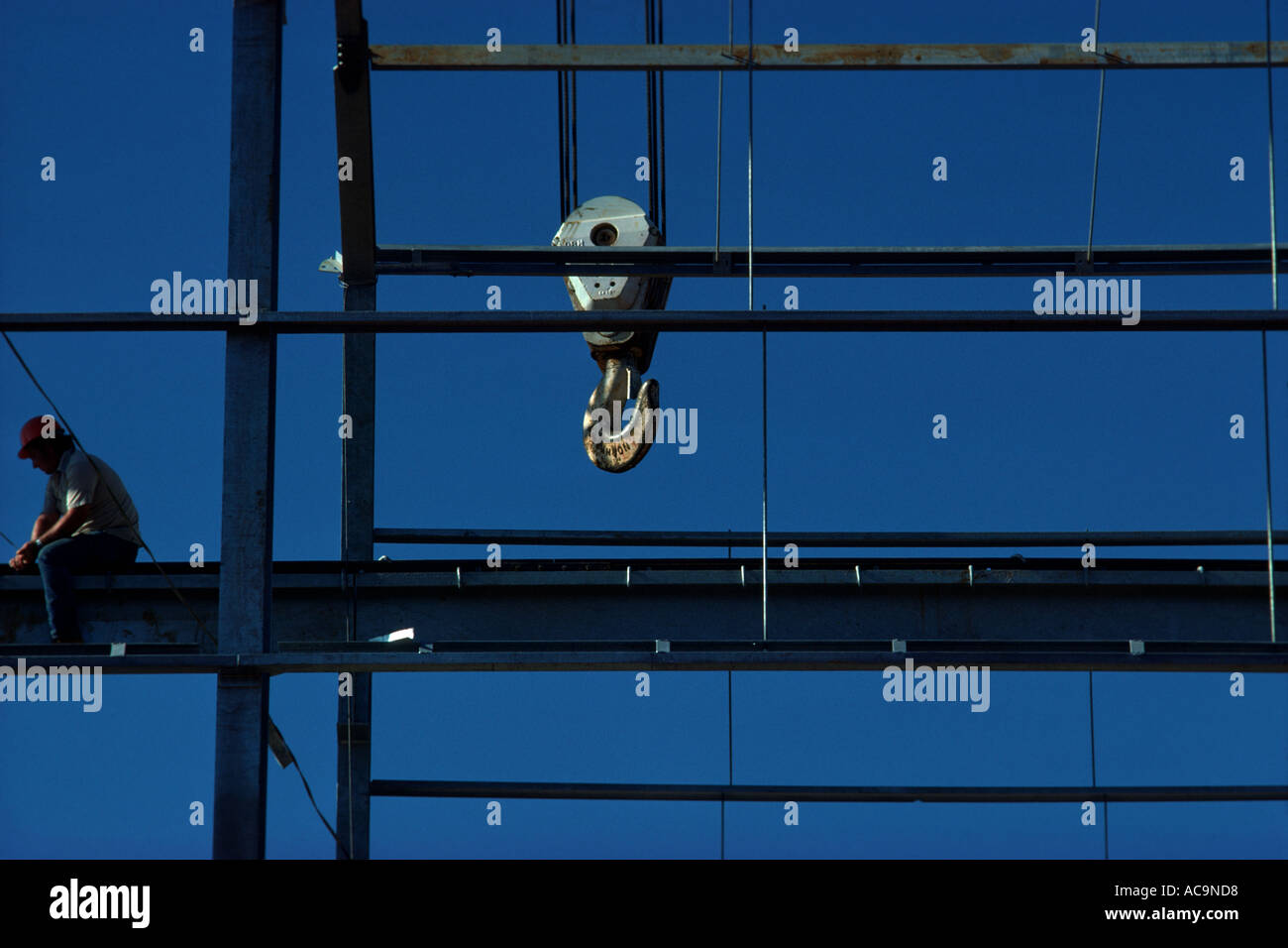 A blue collar worker sits several stories high at a construction site - Stock Image