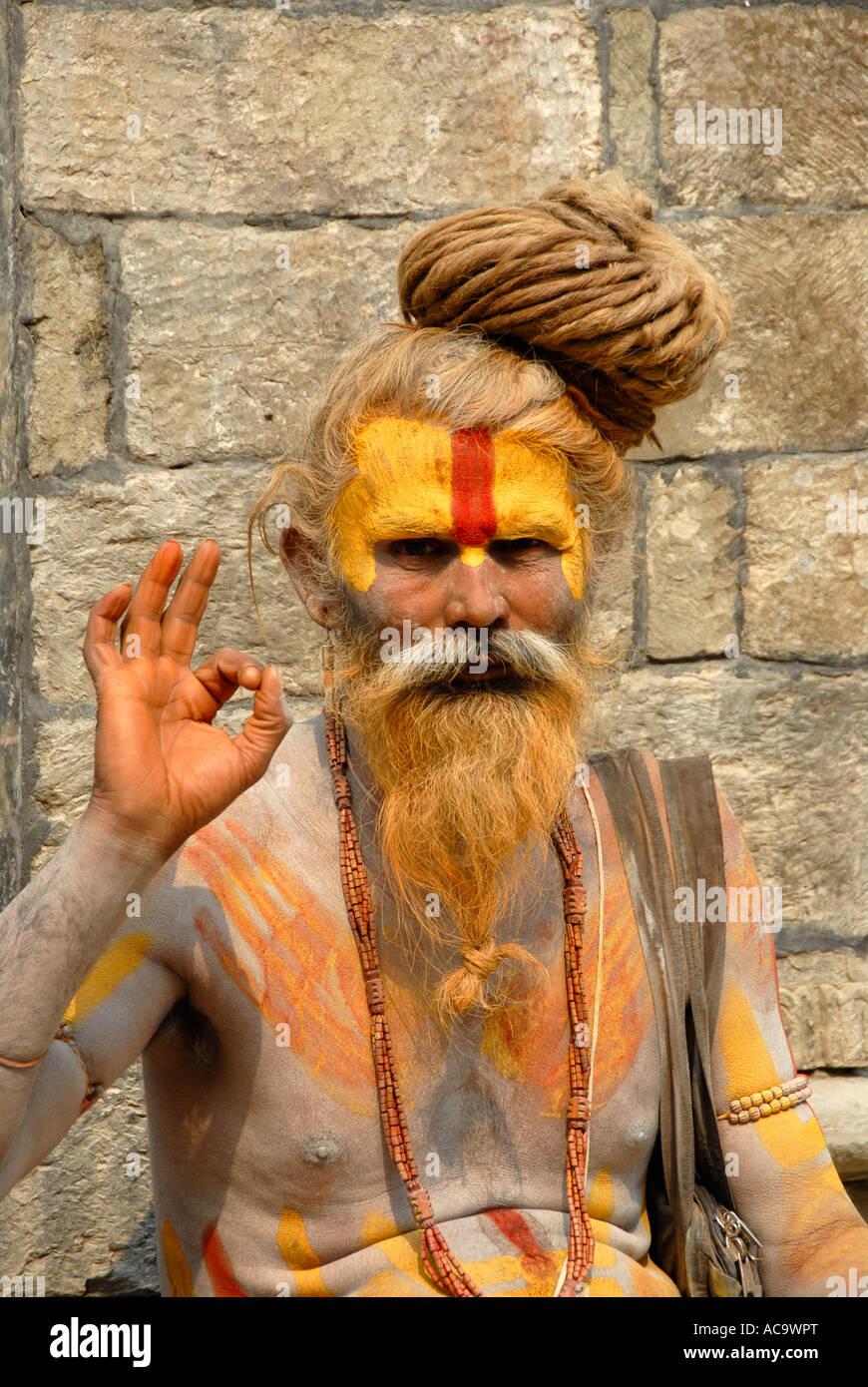 Holy man sadhu blesses colourfully painted Pashupatinath Kathmandu Nepal - Stock Image