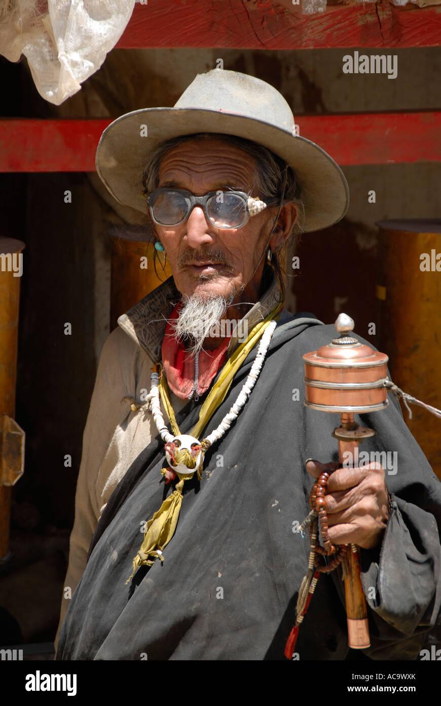 Tibetan Buddhism pilgrim with beard turns prayer wheel Shegar town Tibet China - Stock Image