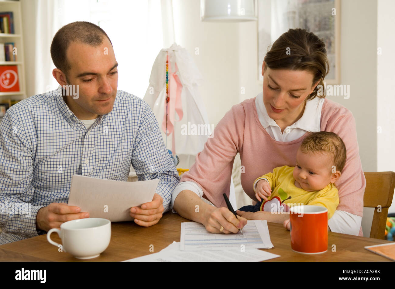 Young family filling out forms for - Stock Image