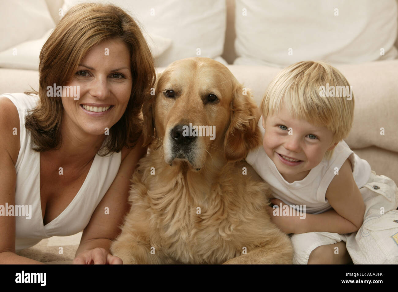 Mother and son inside with family dog - Stock Image
