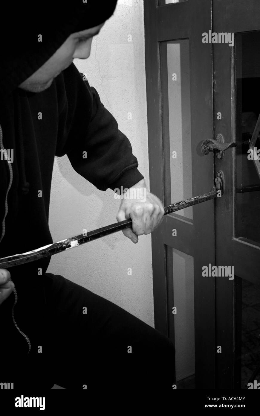 A burglar breaks open a door - Stock Image