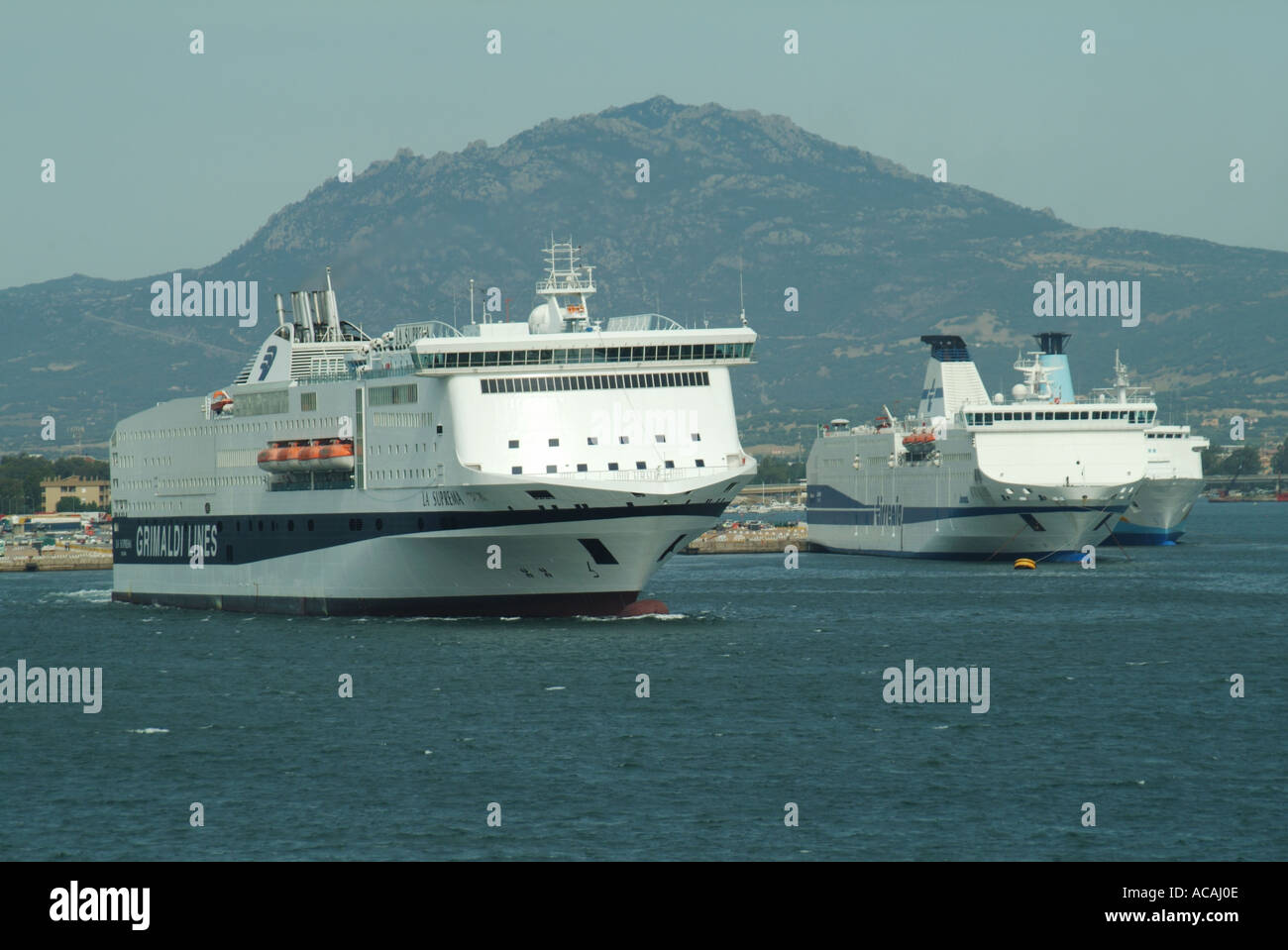 Olbia Sardinia port Grimaldi Lines La Suprema ferry departing with two other ferries at moorings - Stock Image