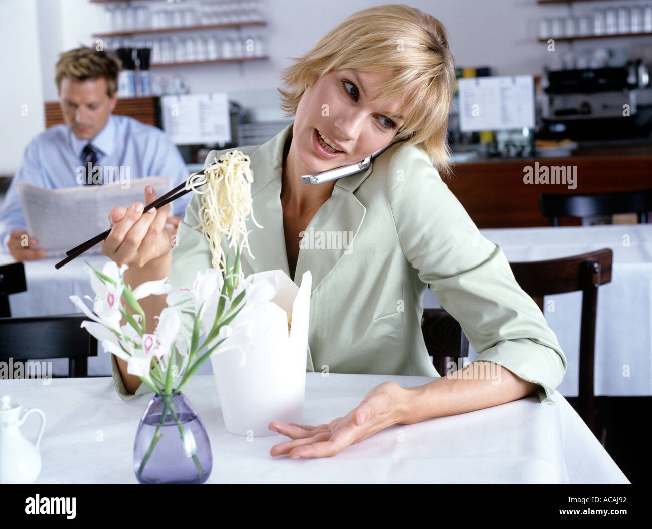 woman eating noodles while talking on mobile businessman reading paper in the background Stock Photo
