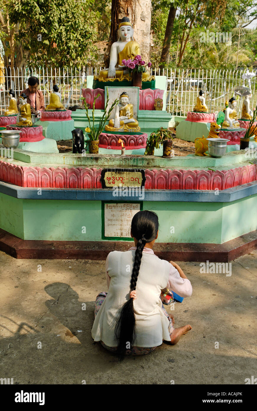Woman in front of a buddhist shrine, Yangon, Myanmar Stock Photo