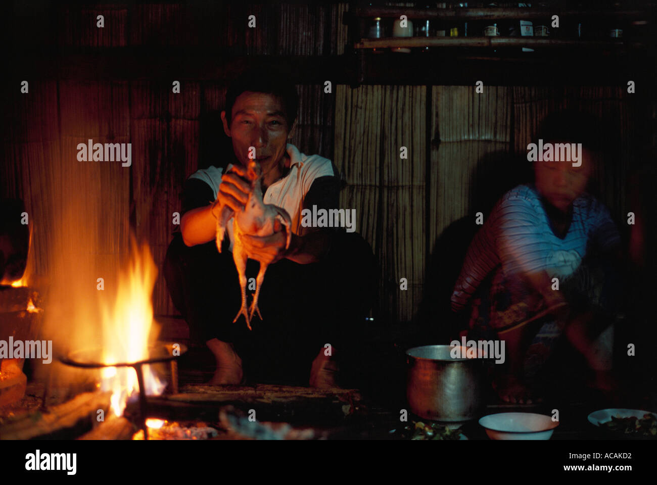 Thai Lahu hilltribe man displays chicken to be cooked over open fire and eaten for evening meal. Woman with motion blur. - Stock Image
