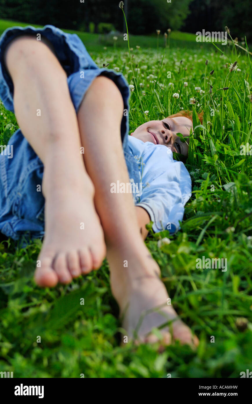 Boy lies barfoot in a meadow - Stock Image