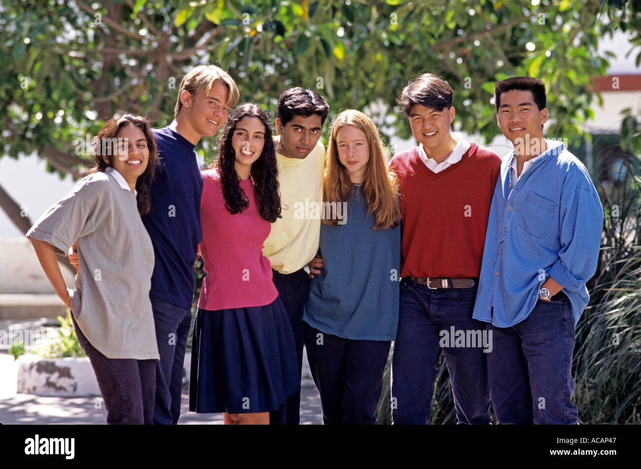 Group of happy senior multiracial teenage school students outside in sunny playground campus - Stock Image