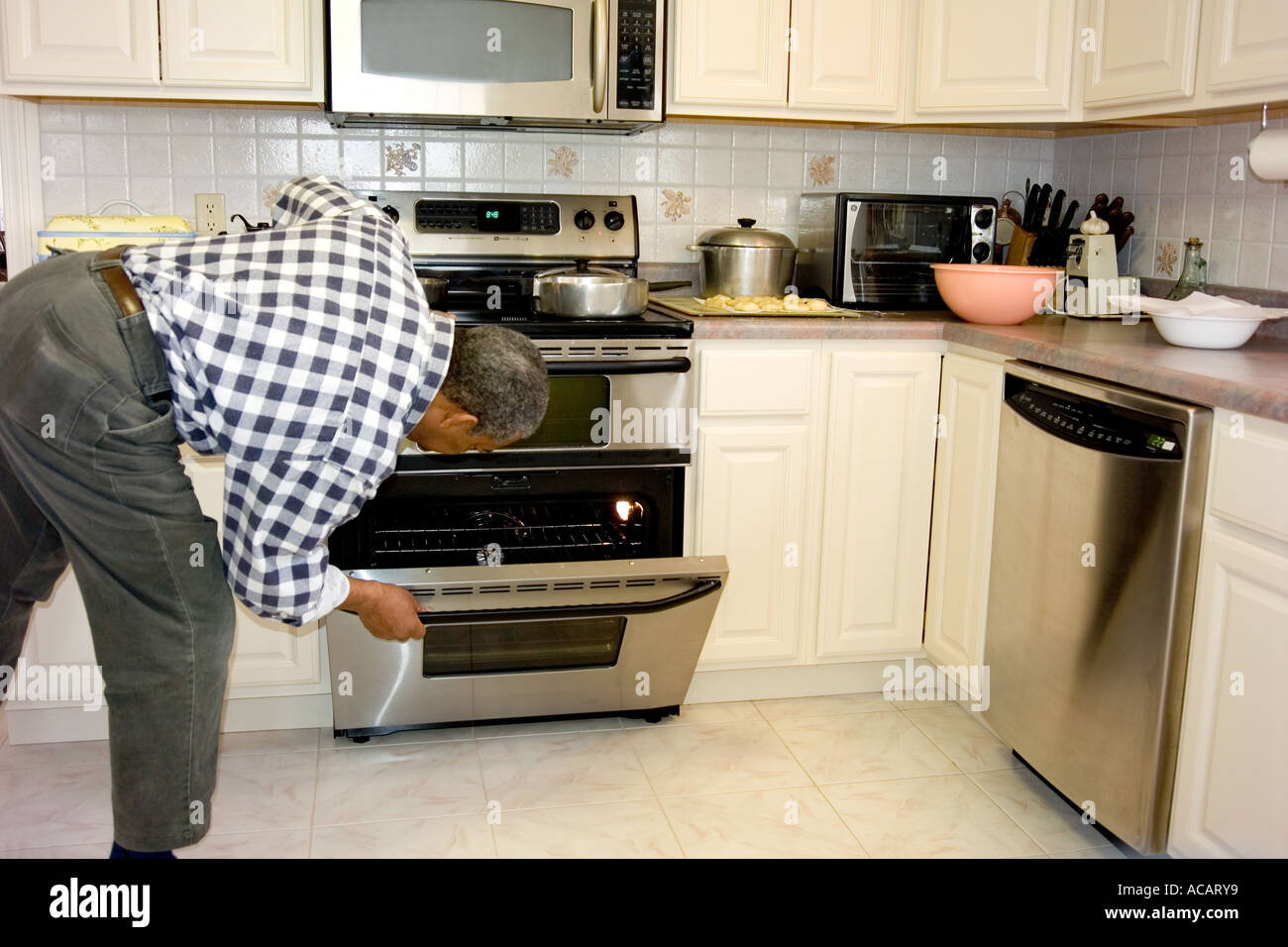 Man in the Kitchen looking in oven - Stock Image