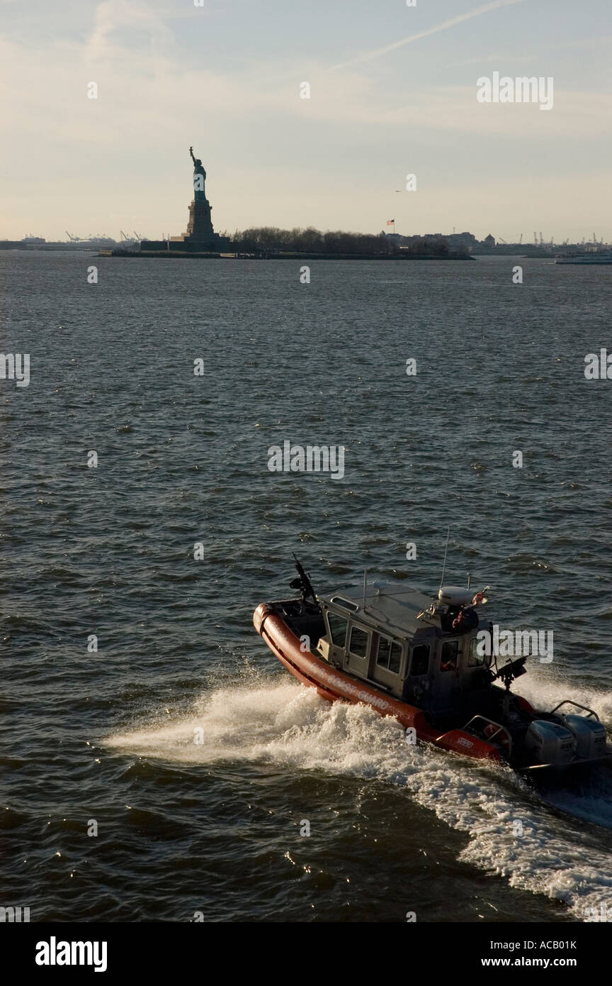 US Coast guard patrolling Upper New York Bay in front of Statue of Liberty - Stock Image