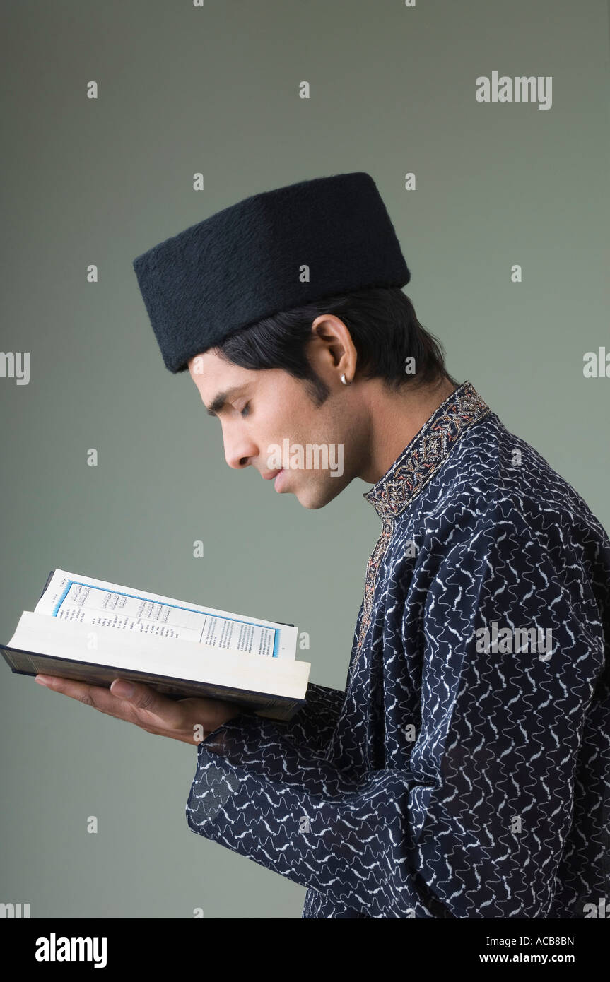 Side profile of a young man reading the Koran - Stock Image