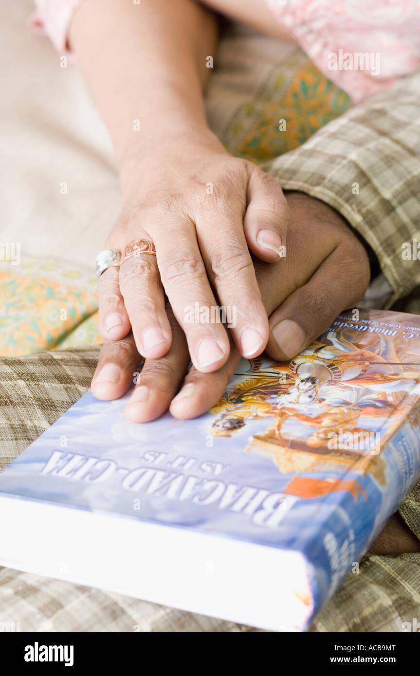 Close-up of couple's hands on the Bhagavad-Gita - Stock Image