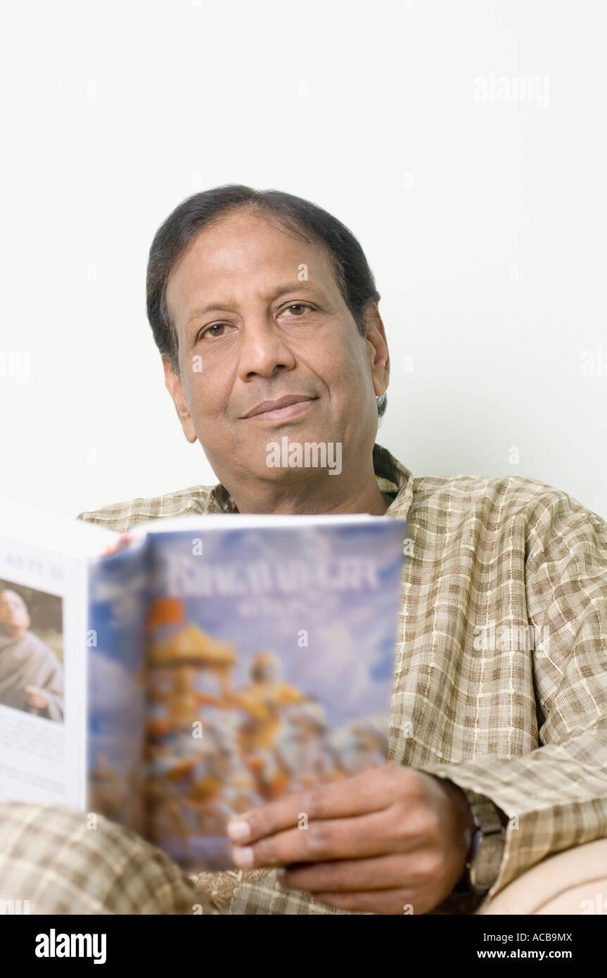 Portrait of a mature man holding the Bhagavad-Gita - Stock Image
