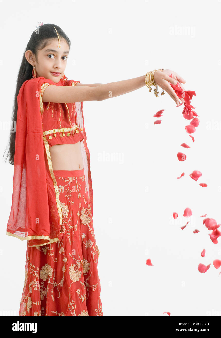 Portrait of a girl in traditional clothes dropping rose petals - Stock Image