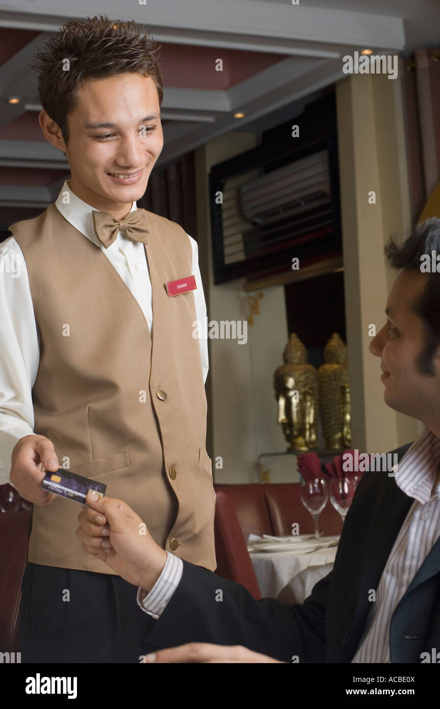 Young man paying a bill with a credit card - Stock Image