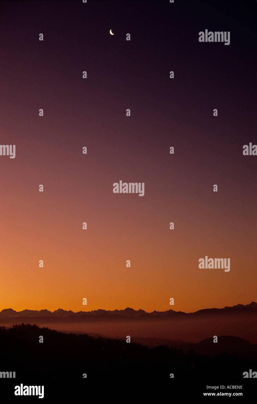 declining moon at evening swiss alpes switzerland - Stock Image