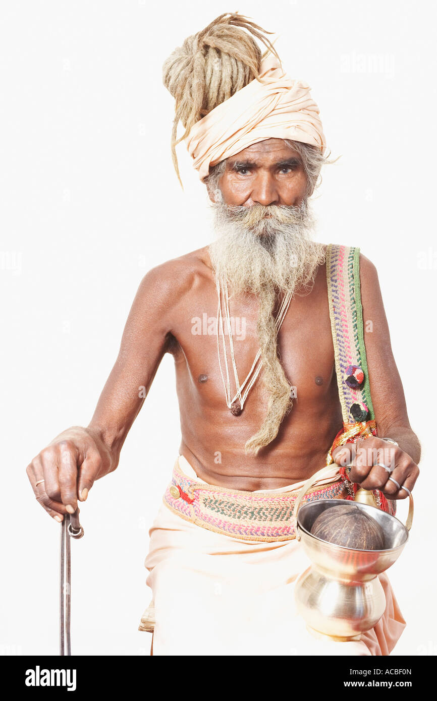 Portrait of a sadhu holding a cane and a kamandal - Stock Image