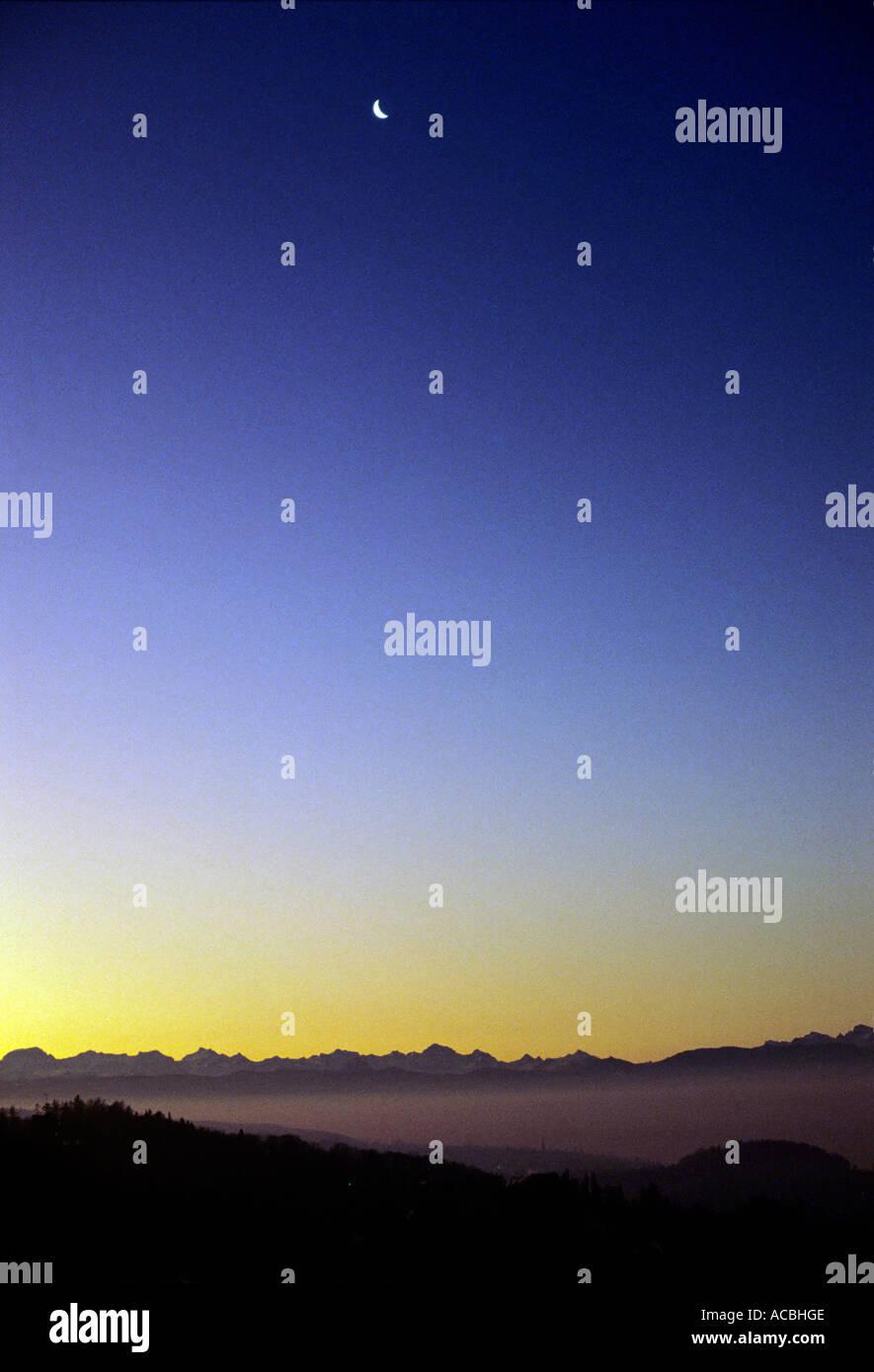 digital enhancement declining moon at morning swiss alpes switzerland - Stock Image